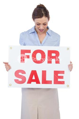 Happy estate agent posing with for sale sign