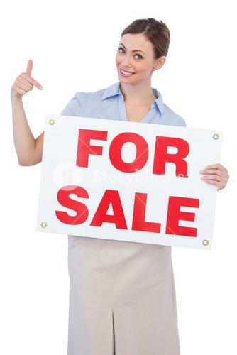 Happy estate agent posing and pointing to for sale sign