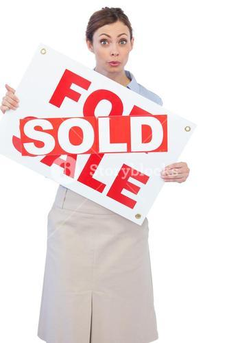 Estate agent showing for sale sign with sold sticker across it