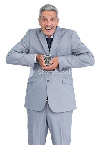 Cheerful businessman with alarm clock in both hands