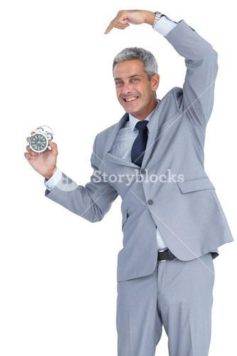 Cheerful businessman pointing out alarm clock