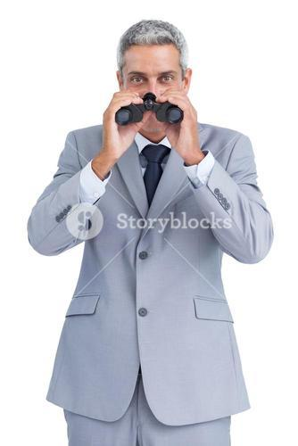 Curious businessman observing through binoculars