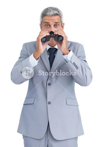 Curious businessman observing with binoculars