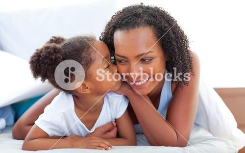 Cute little girl woman kissing her mother lying down on bed