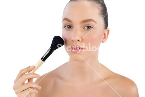 Model applying face powder with brush