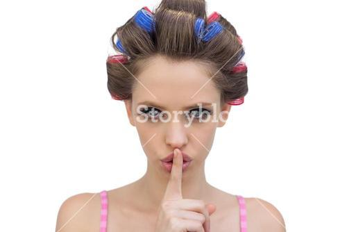 Model in hair rollers posing with finger on mouth