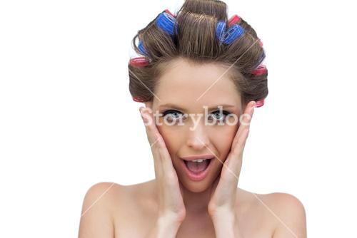 Astonished model in hair rollers posing