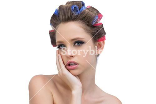 Pensive young woman in hair curlers posing and looking