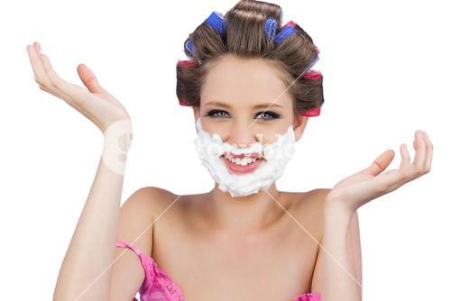 Cheerful woman with hands up and shaving foam on face