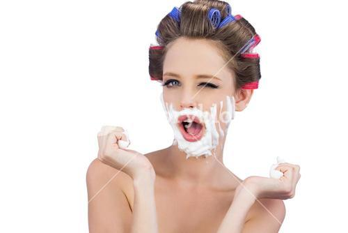 Cheeky model in hair curlers posing with shaving foam