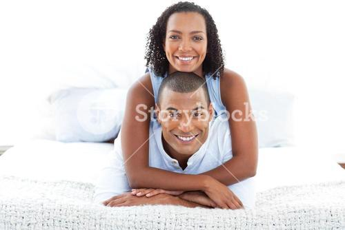 Portrait of an intimate couple cuddling lying down on bed