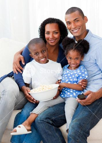 Portrait of a family eating popcorn and watching TV