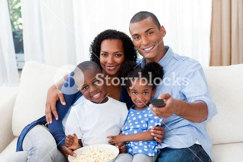 Smiling family eating popcorn and watching TV