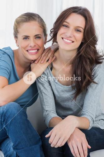 Delightful friends posing while sitting on the couch