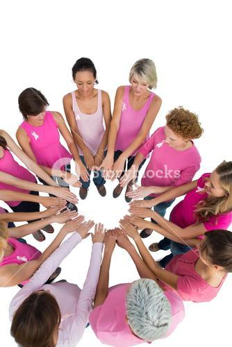 Happy women joined in a circle and looking at each otherwearing pink for breast cancer