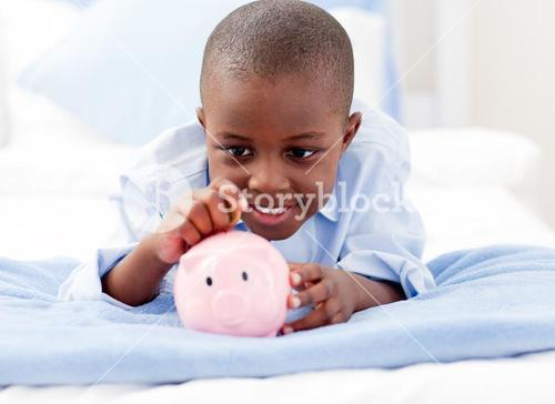 Young Boy on a bed putting money into a piggy bank