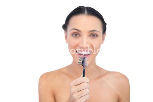 Enthusiastic young model holding eyebrow brush in front of her