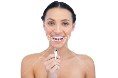 Enthusiastic young brunette holding nail clippers