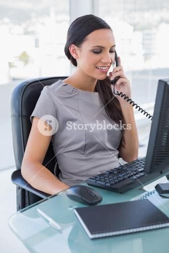 Smiling sexy businesswoman answering phone