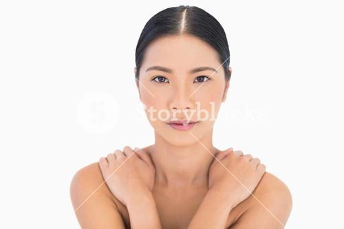 Natural dark haired model posing hands on shoulders