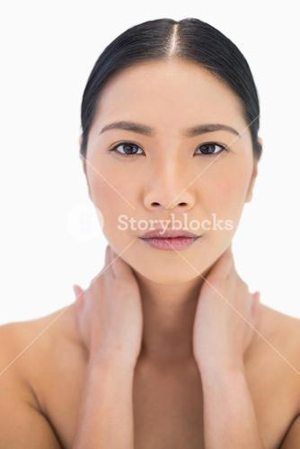 Serious pretty natural model posing with hands on her neck