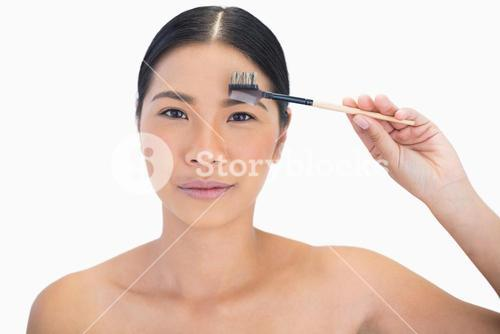 Peaceful gorgeous natural model using eyebrow brush