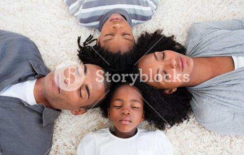 Family sleeping on floor with heads together