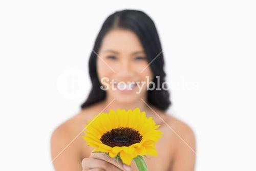Smiling natural model holding sunflower in her hand