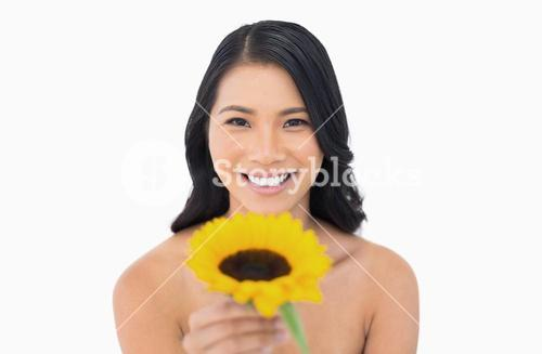 Cheerful natural model holding sunflower in her hand