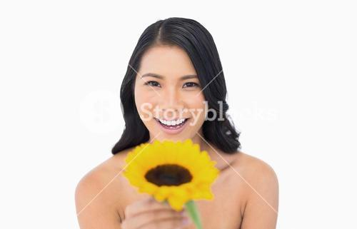 Happy natural model holding sunflower in her hand