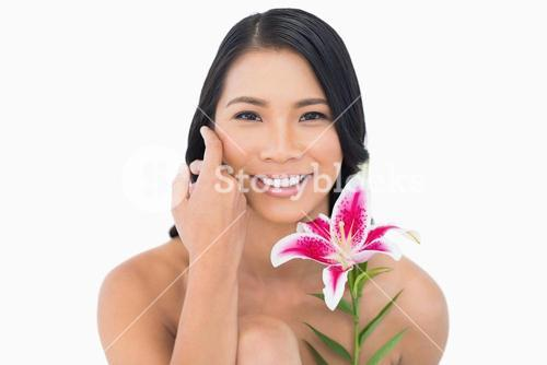 Smiling natural model posing with lily and caressing her face