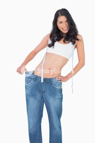 Smiling sexy woman wearing too big pants