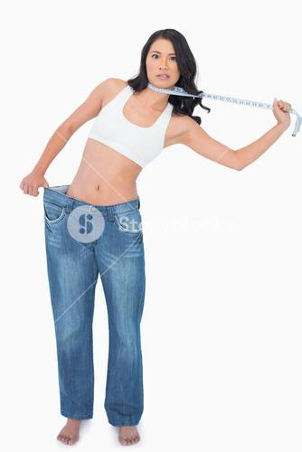 Sexy woman wearing too big pants and strangling herself with measuring tape