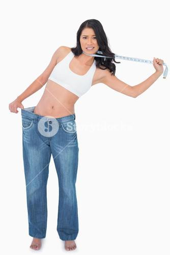 Woman wearing too big pants and strangling herself with measuring tape
