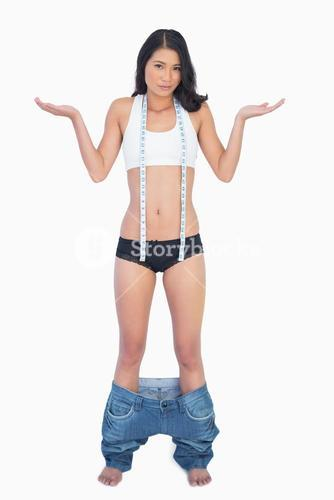 Surprised woman wearing jeans falling down because shes lost weight