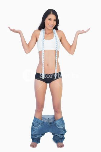Smiling woman wearing jeans falling down because shes lost weight