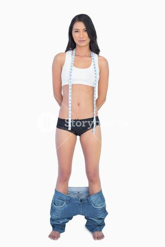 Self confident woman wearing jeans falling down because shes lost weight