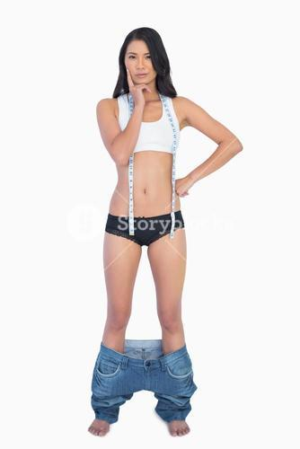 Pensive woman wearing jeans falling down because shes lost weight