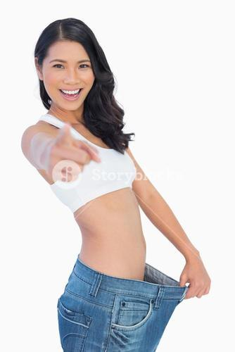 Victorious woman holding her too big pants and pointing out at camera