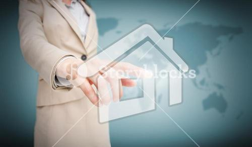 Businesswoman touching house graphic