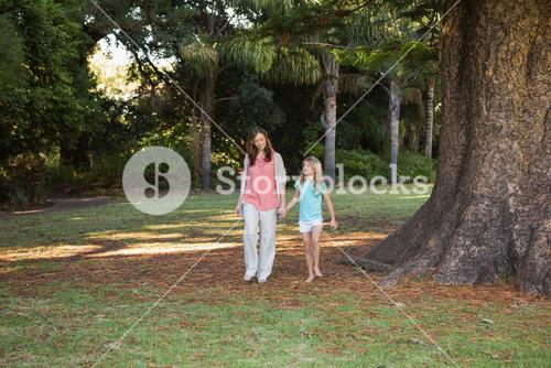 Mother and daugther walking in a park