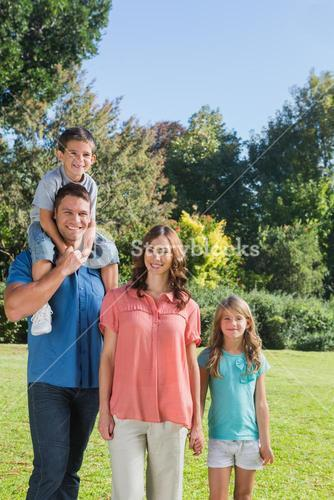 Young family posing in a park