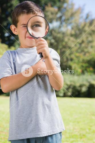 Small child looking through a magnifying glass