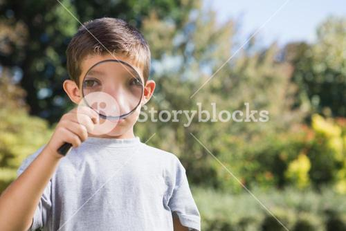 Cheerful boy looking through a magnifying glass