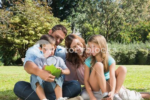 Happy family in a park with father and son inspecting leaf with magnifying glass