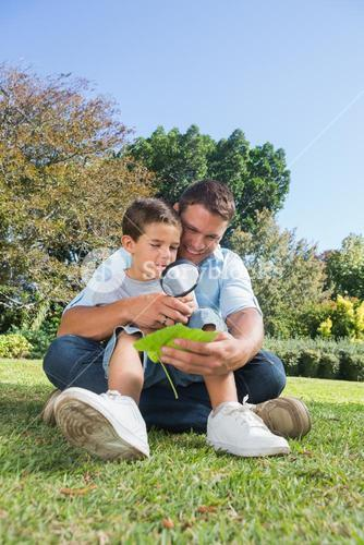 Happy dad and son inspecting leaf with a magnifying glass