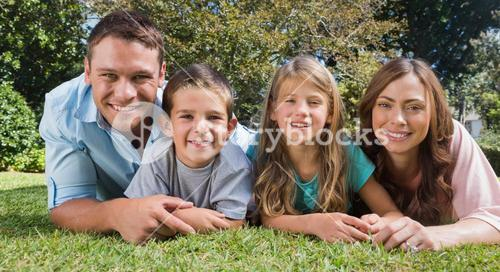 Smiling family lying on the grass