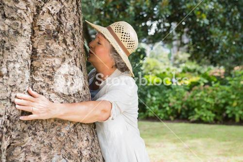 Retired woman hugging a tree