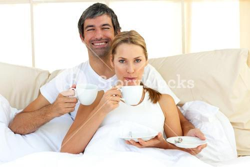 Intimate couple drinking coffee lying in the bed