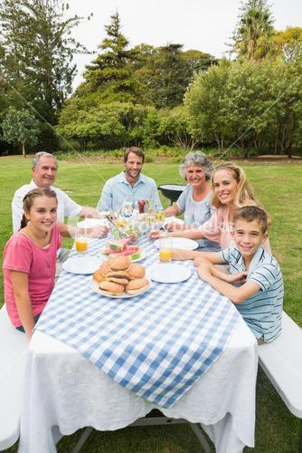 Happy extended family having dinner outdoors at picnic table